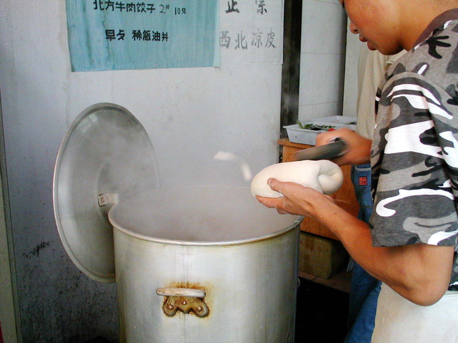 蘇州のラーメン屋さん、削りながら鍋に入れています